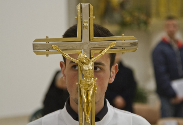 A crucifix is held by a young priest during the Easter Vigil mass at Mother Teresa Cathedral in Kosovo capital Pristina Saturday, April 4, 2015 as Catholics ...