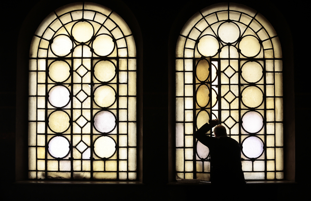 A man breaths fresh air through an opened window during a holy mass marking Orthodox Christian feast of Christ's Entry into Jerusalem (Palm Sunday) at Alexan...