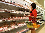 A woman shopping at refridgerated meat counter in supermarket in England.  B2DNG2