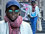 """10/18/15 NYC - Lupita Nyong'o goes incognito in a blue cap and shades as she walks in soho with her printed bag, """"Doing Things"""" and leather, letter jacket, """"Ratta"""" wearing denim flare jeans in Soho on Sunday October 18th, 2015. Non-Exclusive / Luis Yllanes / Splash News\n\nPictured: Lupita Nyongo\nRef: SPL1154687  181015  \nPicture by: Luis Yllanes / Splash News\n\nSplash News and Pictures\nLos Angeles: 310-821-2666\nNew York: 212-619-2666\nLondon: 870-934-2666\nphotodesk@splashnews.com\n"""