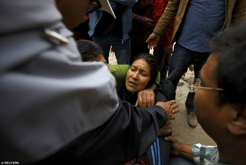A woman cries after she finds out her son was trapped inside a house which collapsed in the Nepal earthquake which also sparked a deadly avalanche on Mount Everest