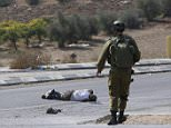 ATTENTION EDITORS - VISUAL COVERAGE OF SCENES OF INJURY OR DEATH An Israeli soldier stands next to an Israeli motorist after he was struck by a Palestinian vehicle in the West Bank city of Hebron October 20, 2015. A Palestinian vehicle ran over and killed an Israeli motorist whom a Reuters photographer said was using a club to hit Palestinian protesters and cars on a roadside in the Israeli-occupied West Bank. Israeli police said the man had stopped his car after stones were thrown at it. The driver of the Palestinian vehicle, which the photographer said the Israeli had hit with his club, later turned himself in to Palestinian police. Neither they nor Israeli police commented immediately on whether they believed he had struck the Israeli deliberately. REUTERS/Mussa Qawasma   TEMPLATE OUT.