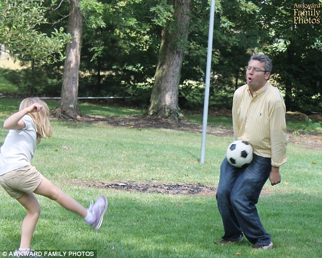 Ouch! A father is caught looking pained at the very moment his daughter kicks a soccer ball into his crotch