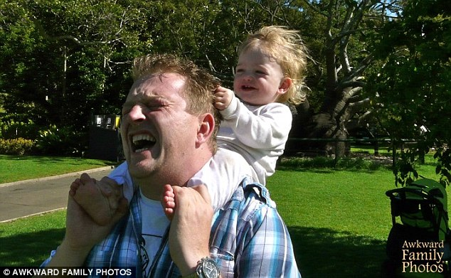 That has to hurt: Another painful looking photo shows a dad giving his daughter a ride on his shoulders. She thanks him by tugging his hair, causing him to wince in agony