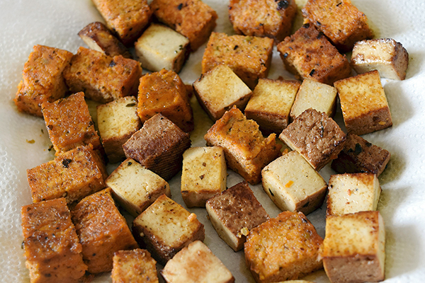 Once lightly browned, set aside on a kitchen paper. Thread on to the skewers alternating tofu and tomatoes. Arrange on a bed of greens.