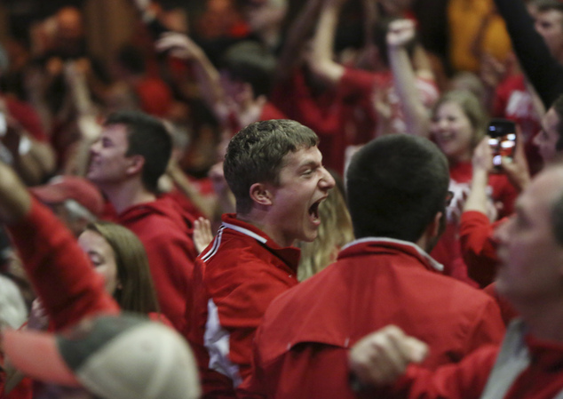 Wisconsin fans, including Taylor Shuster, center, react as they watch television coverage Saturday, April 4, 2015, in Madison, Wis., of Wisconsin taking on K...