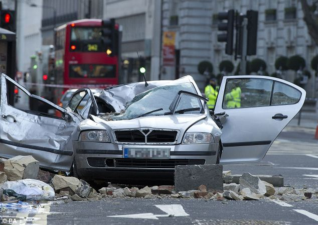 A woman has died after part of a building collapsed onto the car she was driving on High Holborn