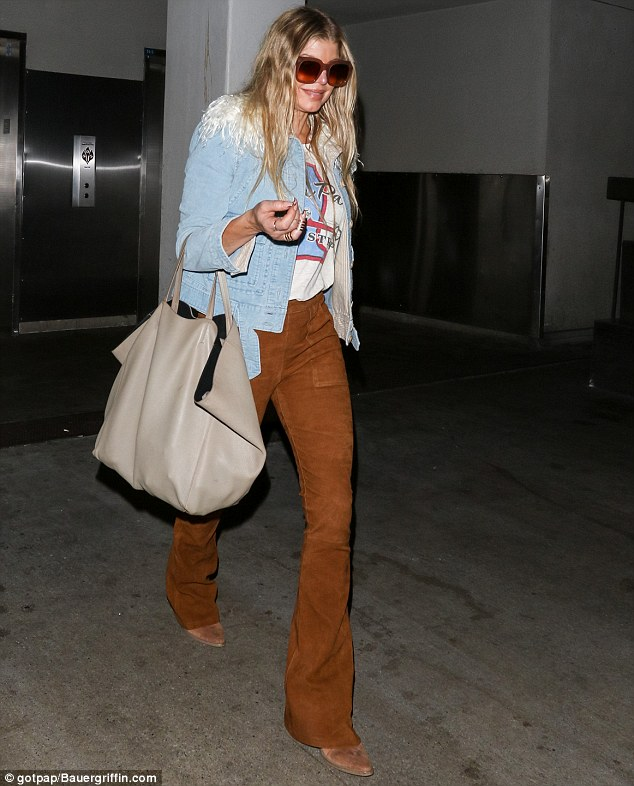 Arriving home: Fergie flew into LAX in the early hours of Thursday morning Wednesday dressed in brown suede trousers, a denim jacket and boots that wouldn't have looked out of place on a cowgirl