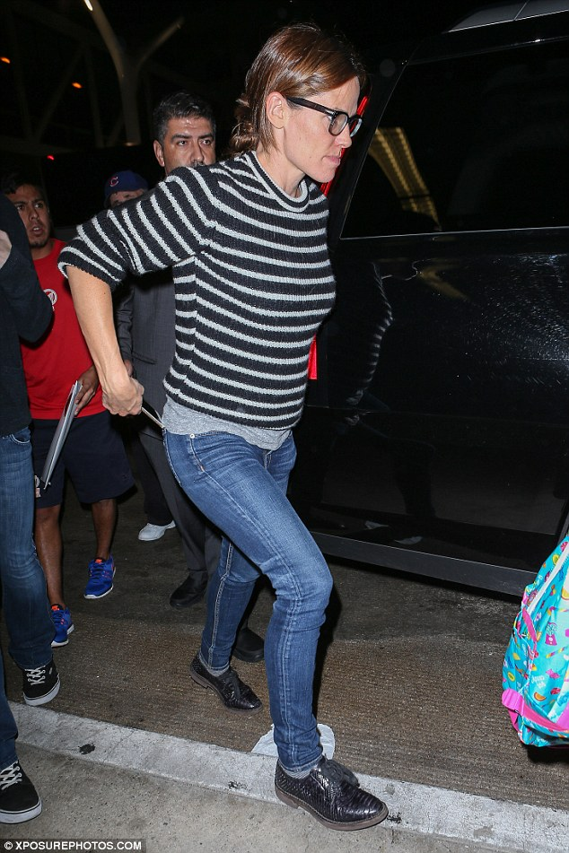 Casual: The actress, 43, was practically dressed for her journey in skinny jeans, a striped sweater and lace-up black shoes. She wore her long hair tied into a messy bun and wore black framed spectacles