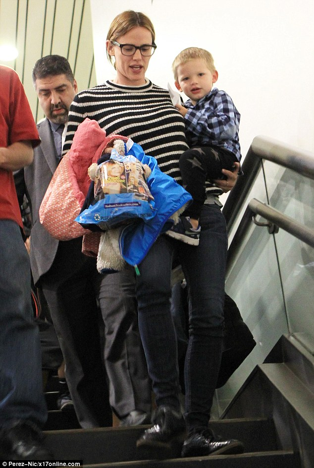 Capable: The 13 Going On 30 standout carried a bag and also afleece-lined jacket for her son as she perched Samuel on her hip. She is still wearing her wedding ring on the middle finger of her left hand