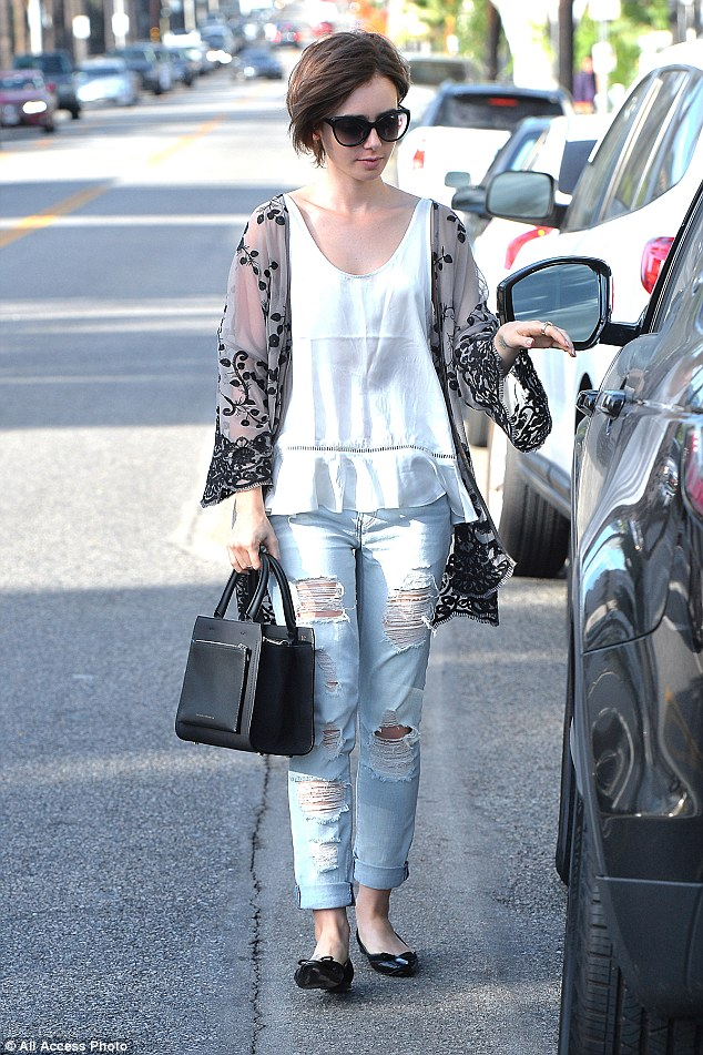 Brunette beauty: Teaming her top with a pair of ripped and distressed denim jeans, Lily - the daughter of British musician Phil Collins - added a rock 'n' roll edge to her laid-back look in her turn-up jeans
