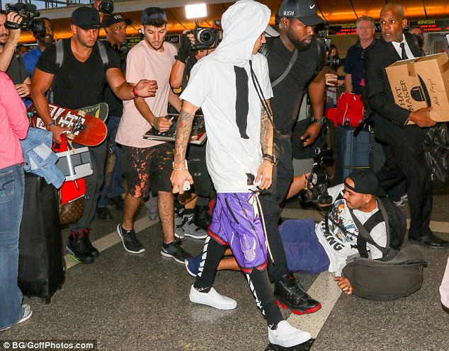 In demand: Justin was followed by a crowd of cameras, with one photographer appearing to fall in the rush