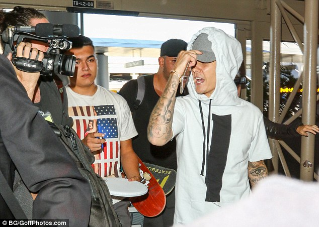 Making a dash for it: The star appeared keen to get to his gate, covering his face with his hat