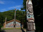 ALASKA, UNITED STATES - 2013/08/20: Tlingit totem pole with clan house in the background at the Totem Bight State Historical Park in Ketchikan, Southeast Alaska. (Photo by Wolfgang Kaehler/LightRocket via Getty Images)