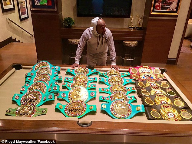 Floyd Mayweather poses with his belts alongside the caption 'It took 19 years but they'll talk about it forever'