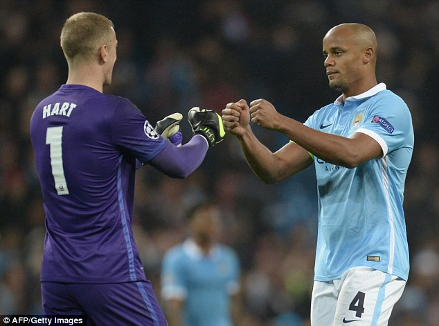 Joe Hart and Vincent Kompany (right) celebrate Manchester City's 2-1 win over Sevilla in midweek