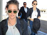 Kristen Stewart and her new pink-haired girlfriend arrive in Los Angeles.  Kristen dressed casual for the flight, in jeans and sneakers, with a t-shirt and un-buttoned button-up.  Saturday, October 24, 2015 X17online.com