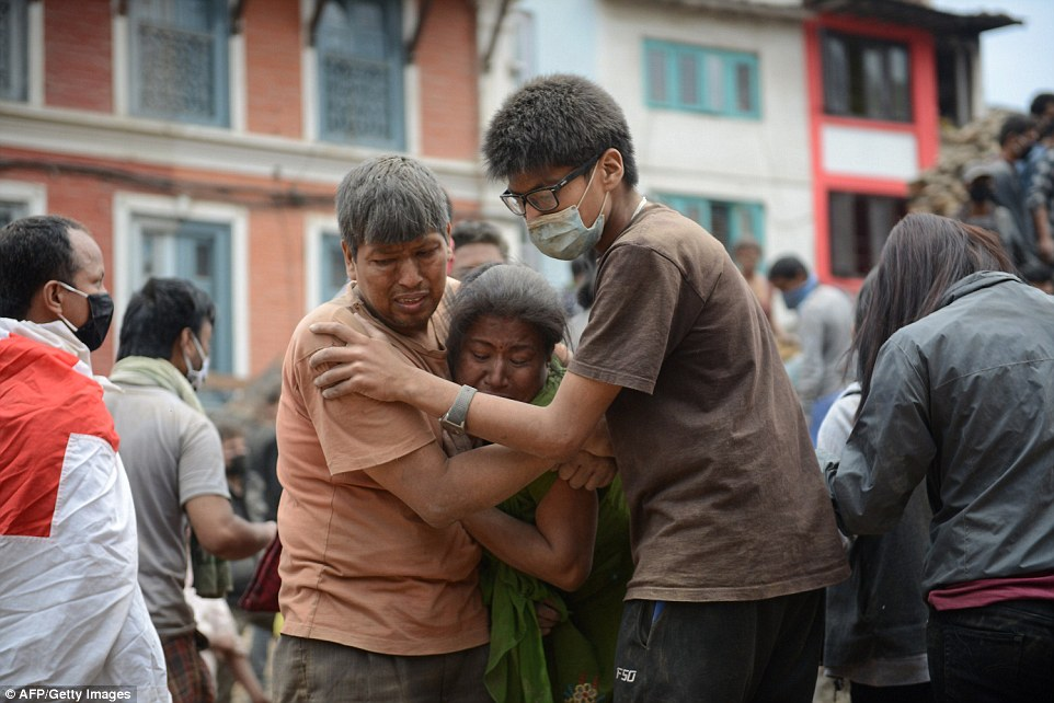 A couple of earthquake victims are helped by a rescuer in Kathmandu's Durbar Square, a UNESCO World Heritage Site that was severely damaged by the earthquake