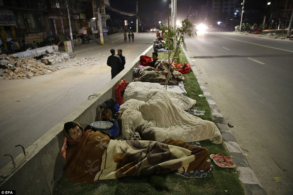 Scared that  tremors might destroy their homes overnight, residents of Kathmandu set up camp on the central reservation of a major road