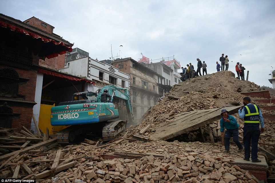 People clear rubble in Kathmandu's Durbar Square, a UNESCO World Heritage Site that was severely damaged by the natural disaster