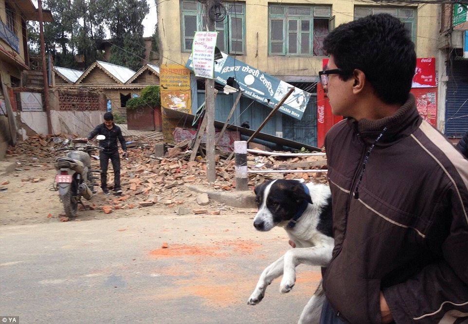 A man carries a dog and as he walks past the rubble of a building which was destroyed by the disaster which hit at midday in the densely populated Kathmandu Valley