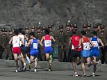 FILE - In this April 14, 2013 file photo, marathon runners pass by a long row of North Korean soldiers as they cross a bridge in Pyongyang as North Korea hosts the 26th Mangyongdae Prize Marathon to mark the birthday of the late leader Kim Il Sung on April 15. For the first time ever, North Korea is opening up the streets of its capital to runner-tourists for the annual Pyongyang marathon, undoubtedly one of the most exotic feathers in any runnerís cap. Tourism companies say they have been inundated by requests to sign up for the April 13, 2014 event, which this year will include amateur runners from around the world. (AP Photo/David Guttenfelder, File)