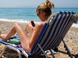 A stock photo of a woman using a cell phone near a beach on Greek island of Kefalonia, Greece.    CFEP82 Lady, woman on beach on Greek island of Kefalonia on sun lounger using mobile phone to phone home. Image shot 10/2011. Exact date unknown.