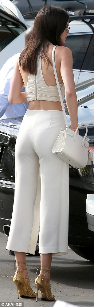 Appropriate for church? The 19-year-old modelwore a more revealing outfit showcasing her toned midriff in a halter crop top and wide leg trousers