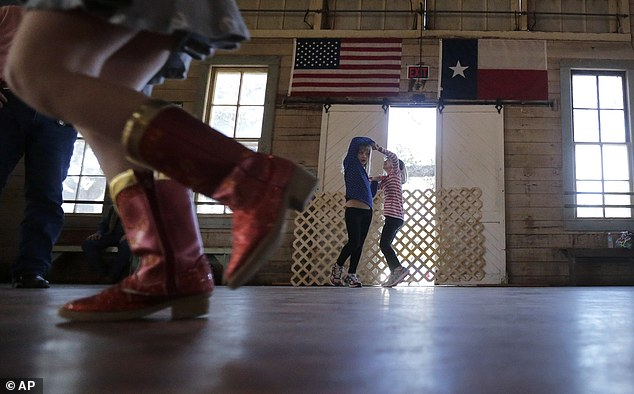 One, two, step! In this December 2014 file photograph, girls dance to fiddle music at Twin Sisters Dance Hall in Blanco, Texas