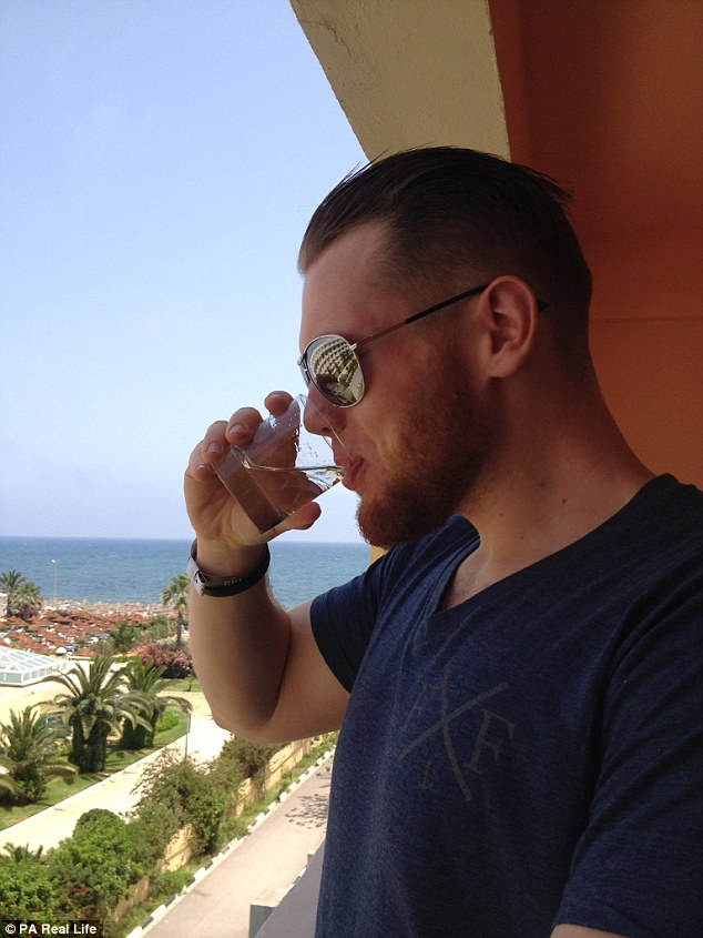Nathan, pictured enjoying a drink on his hotel balcony in Sousse, said Tunisians 'deserve our support' as they 'put themselves at risk'
