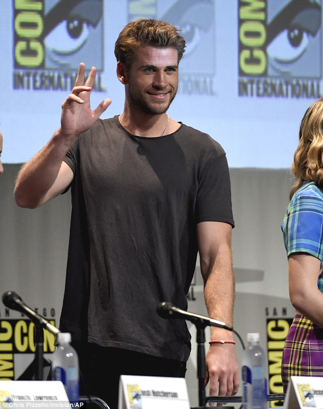 Charming: Liam flashed a smile at the crowd before taking his seat on Thursday