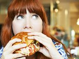 A woman eating hamburger in a cafe.