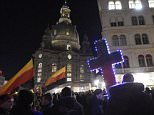 Demonstrators hold an illuminated cross and German flags upside-down during a demonstration of PEGIDA (Patriotic Europeans against the Islamization of the West) in Dresden, eastern Germany, Monday, Nov. 2, 2015. (AP Photo/Jens Meyer)
