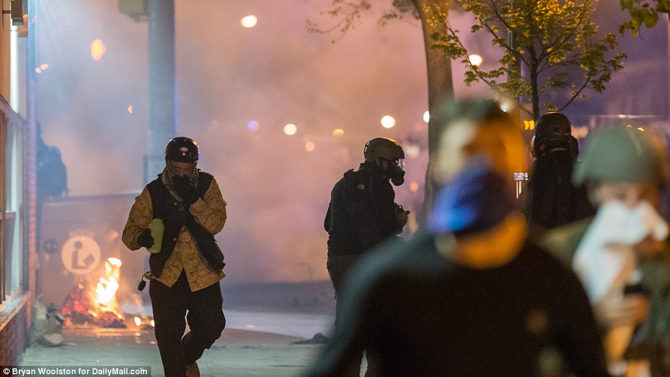 Hard to breathe: Protesters flee after police fire tear gas during protests on West North Ave in Baltimore, Maryland on Tuesday after curfew
