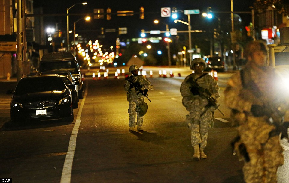 Members of the National Guard walk through the streets of Baltimore, where they were deployed to enforce a 10pm curfew