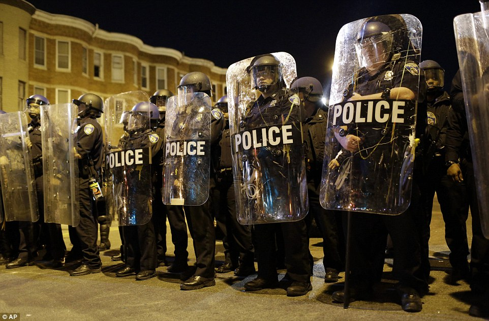 No leaving home: The governor of Maryland promised that the 10pm to 5am curfew would be enforced. Above, police stand in formation before the curfew Tuesday night
