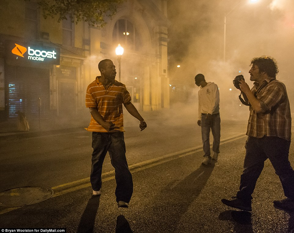 For the camera: A protester celebrates after throwing a gas canister back at police during Tuesday night protests in Baltimore