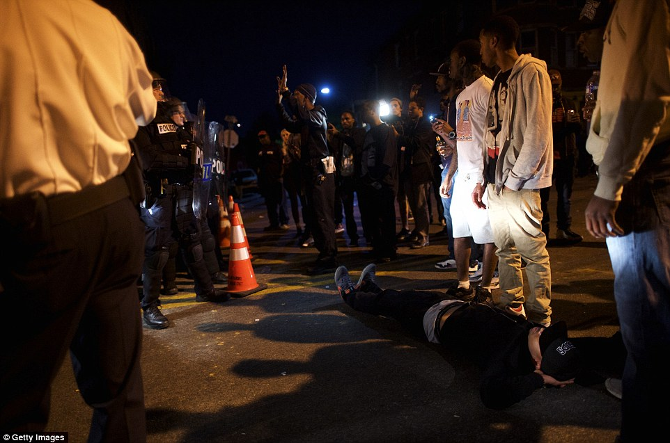 Road block: A protester lies in front of a police barricade blocking the exit of a vehicle the night after citywide riots over the death of Freddie Gray last night in Baltimore, Maryland