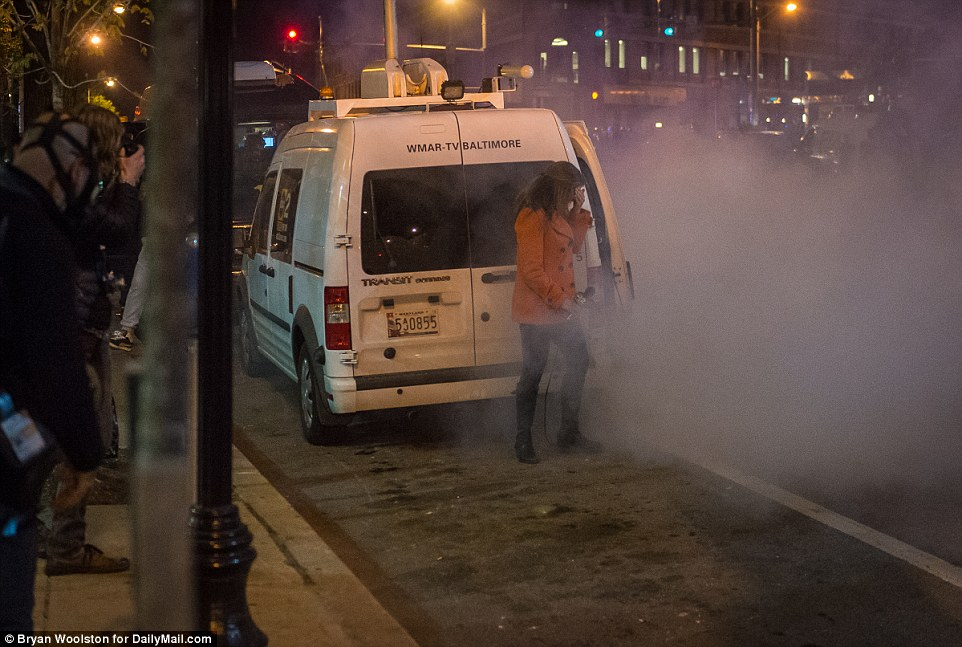 Can't see: WMAR-TV correspondent Catherine Hawley covers her face as she encounters tear gas fired by police during protests on West North Ave in Baltimore, Maryland on Tuesday