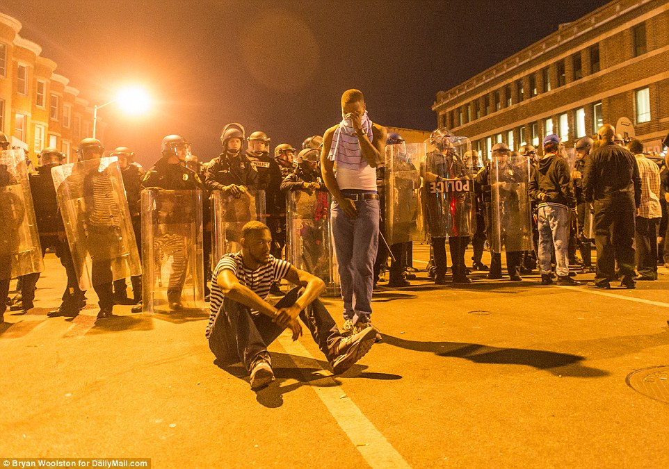 Not moving: Protesters sit in front of police lines on West North Ave during protests in Baltimore on Tuesday