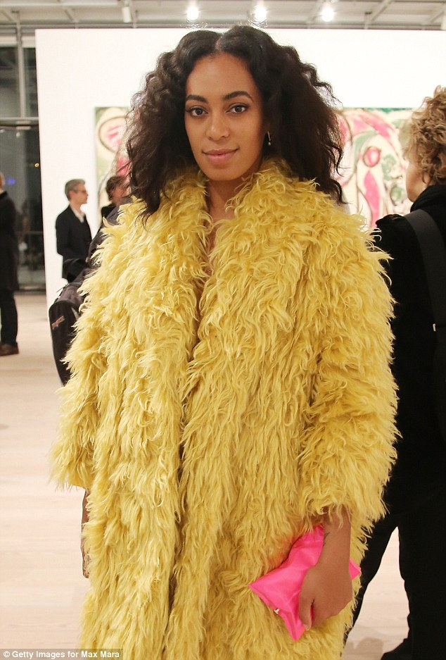 Attention grabbing: Happily posing for pictures at the event, the 28-year-old star covered her lean and slender frame in a glamorous yellow fur coat