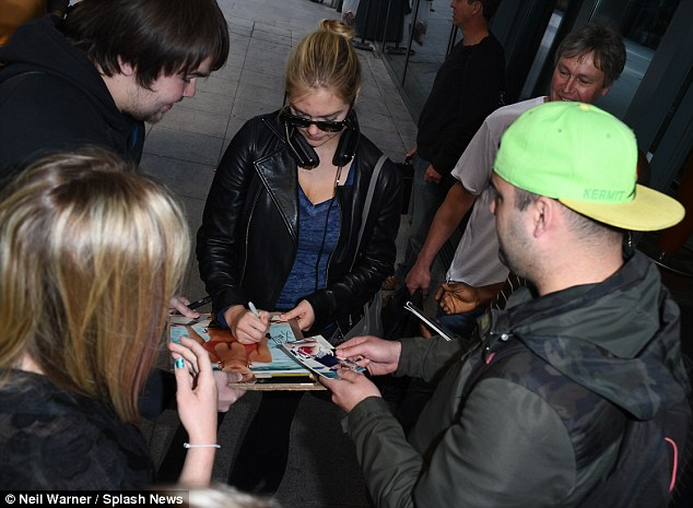 By popular demand: As she exited the bustling terminal, Kate signed autographs for a gathering of fans