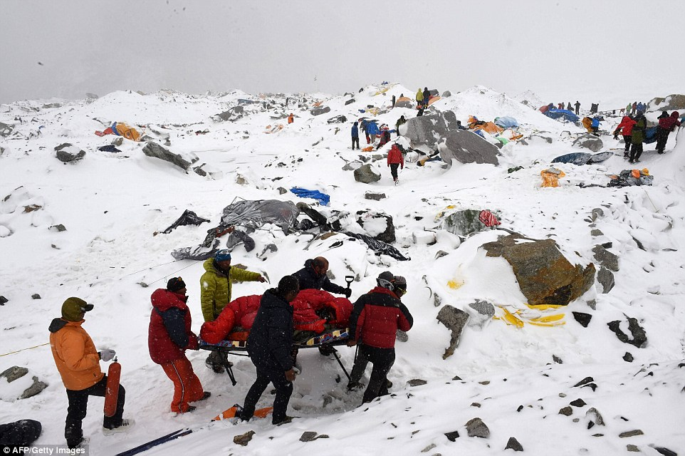 Carried to safety: Rescuers use a makeshift stretcher to carry an injured person after the massive avalanche on Saturday