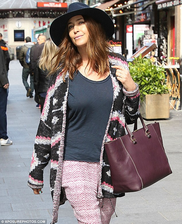 Spring attire: She toted a large burgundy handbag, topping off her ensemble with a black wide-brimmed hat