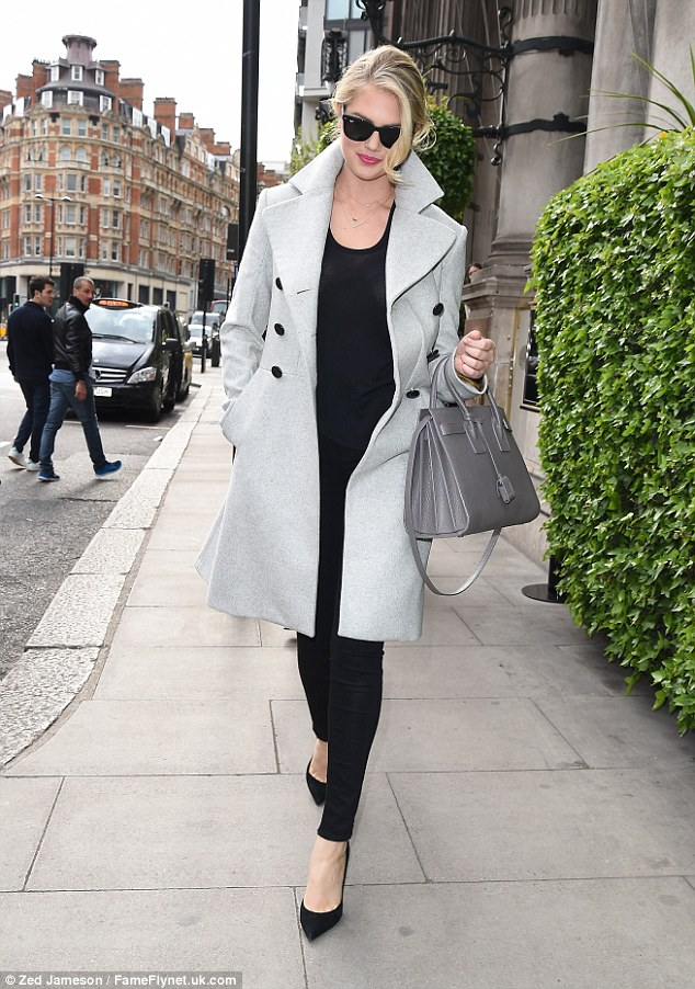 Keeping it casual: The model left her hotel in the English capital, wearing a pair of black skinny jeans, matching top and a grey coat, accessorising the look with heels, sunglasses and a large tote bag