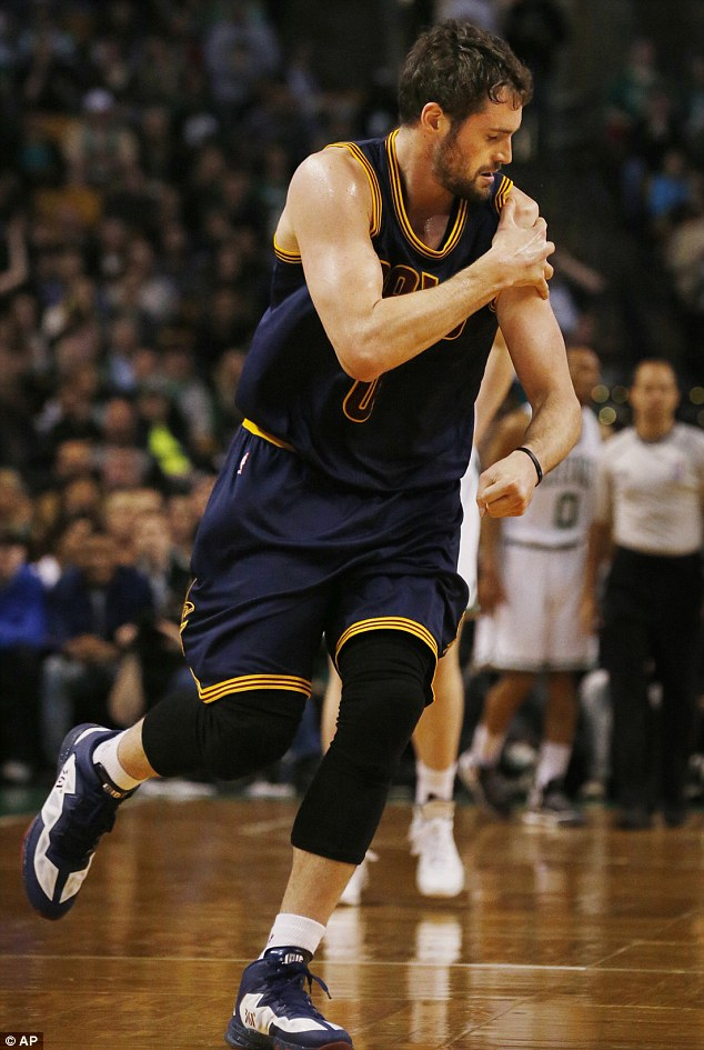 Cleveland Cavaliers forward Kevin Love runs off the floor holding his shoulder during the first quarter of a first-round NBA playoff basketball game in Boston on Sunday