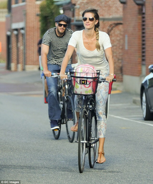 Family time: The Brazlian beauty said she was quitting the runway to spend more time with her family; she was pictured bike riding with husband Tom Brady in Boston on August 20, 2014