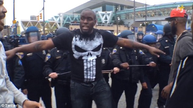 Hero: The man steps in between the crowd and the riot police with his arms held out, as a human barrier