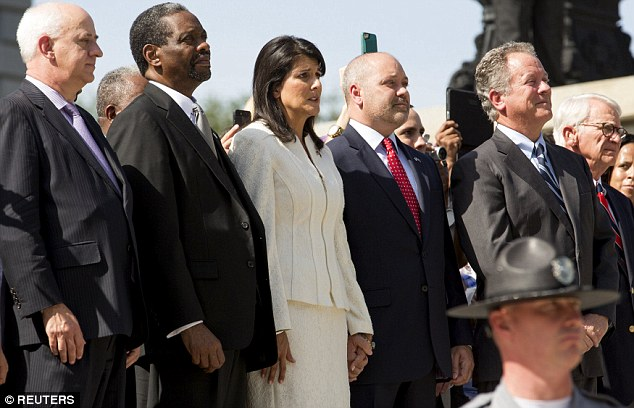 Relieved: Gov Nikki Haley held hands with numerous civil rights figures as it came down