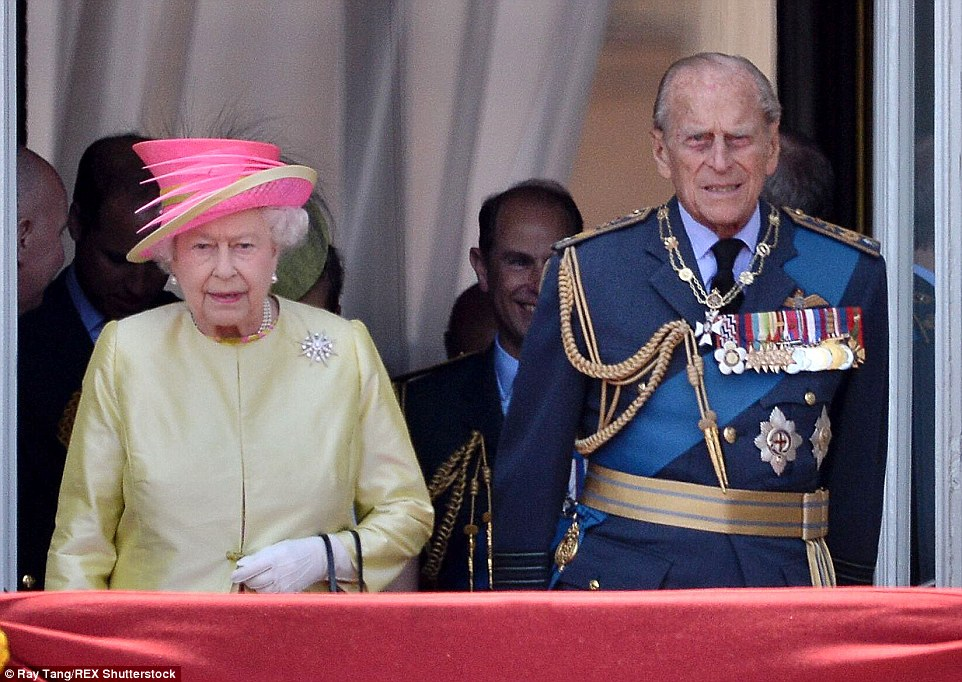 The Queen and the Duke of Edinburgh, pictured together, look out over the crowds gathered outside the gates of Buckingham Palace